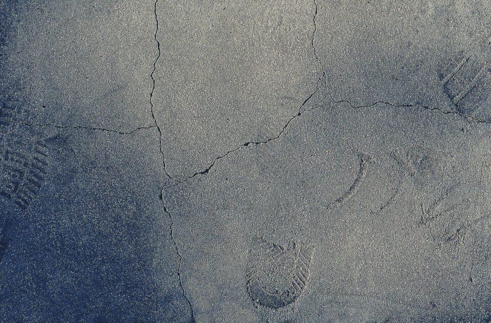 Betonboden mit Spuren und Rissen